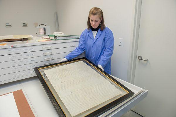 Conservator Leslie Courtois with framed statute.