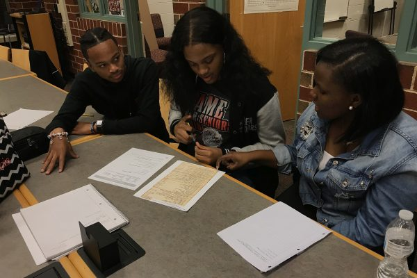 Students discussing an early 1800s estate inventory used in a chancery dispute