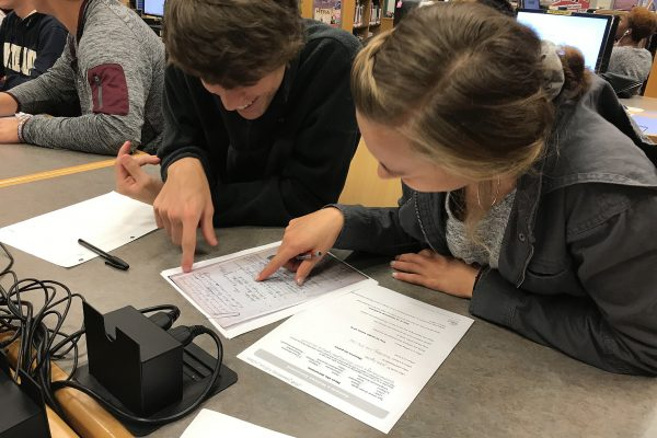 Students reading facsimile of an order in a murder case in a 1700s-era order book
